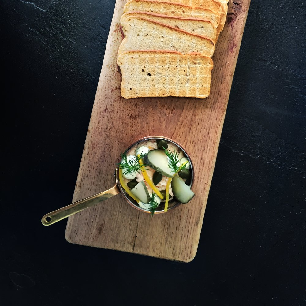 salmon pate served with melba toast, capers, gerkins, preserved lemon and a dill crème fraiche