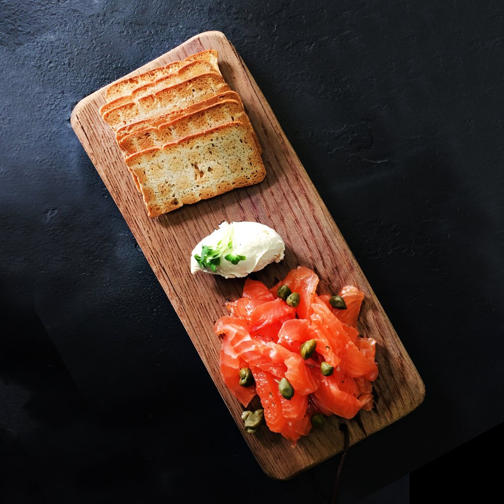 salmon gravalax with capers and creme fraiche and melba toast