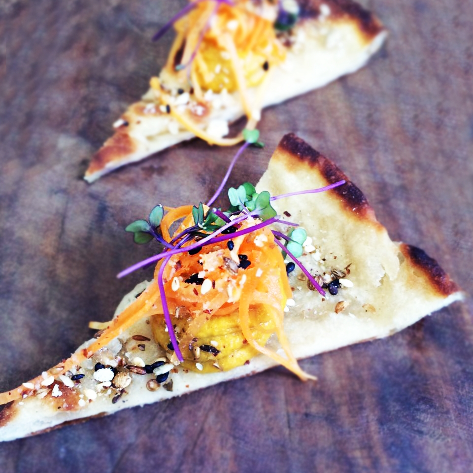 flatbread with turmeric hummus, sesame seeds and pickled carrot