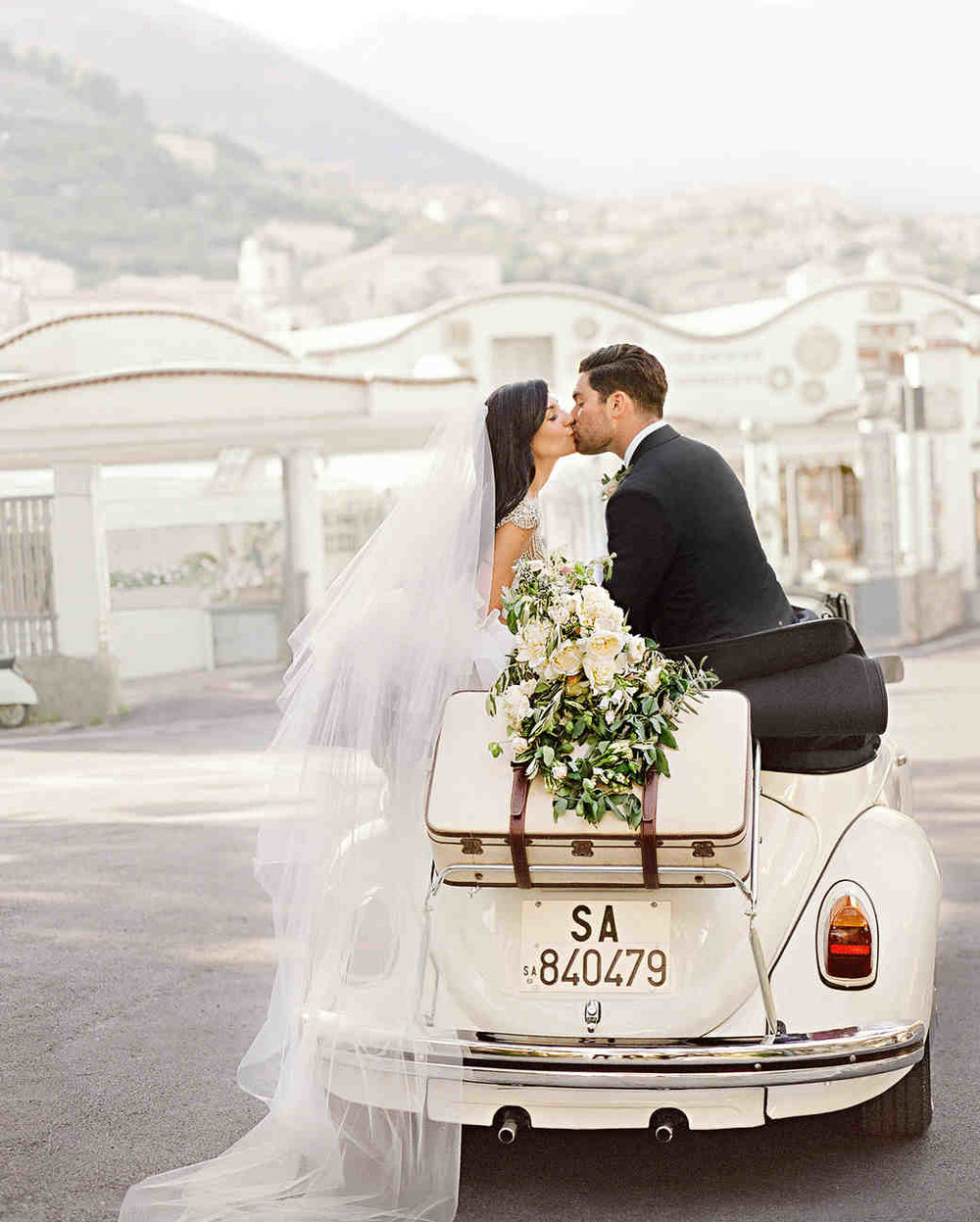couple-wedding-kissing-car-italy-103351309_vert.jpg