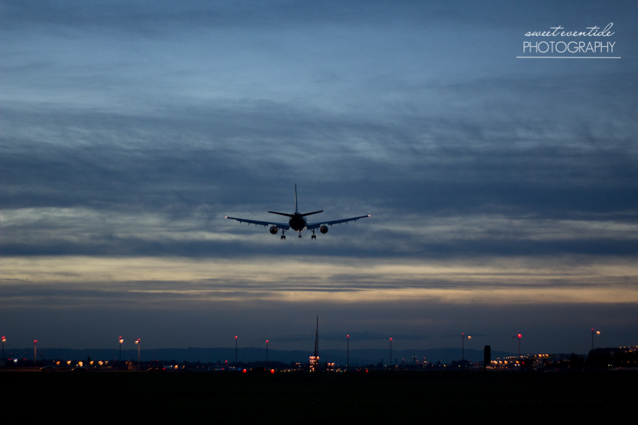 photograph of an airplane landing at portland international airport dusk