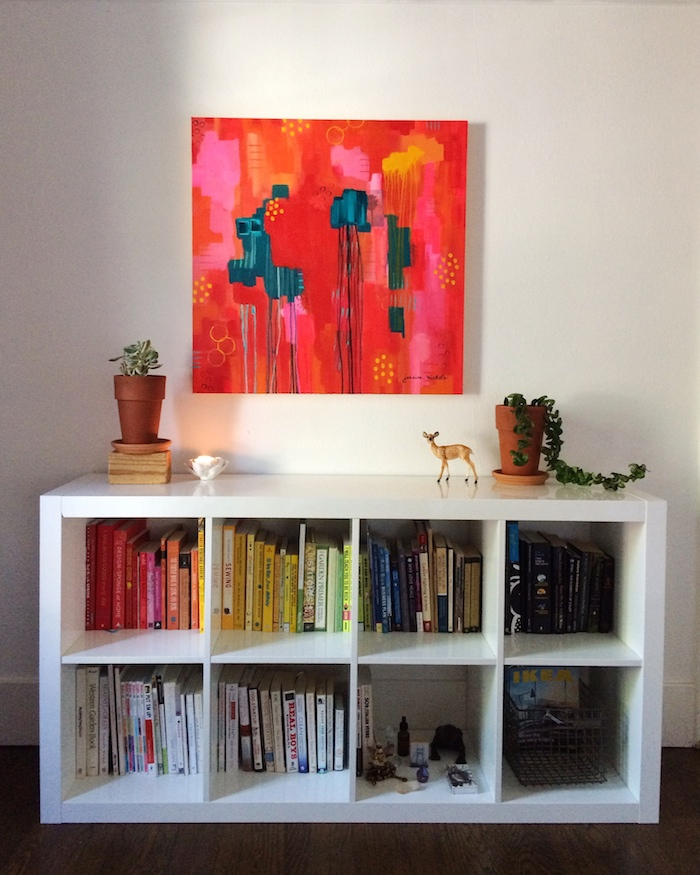 original painting with acrylics hung over bookshelf
