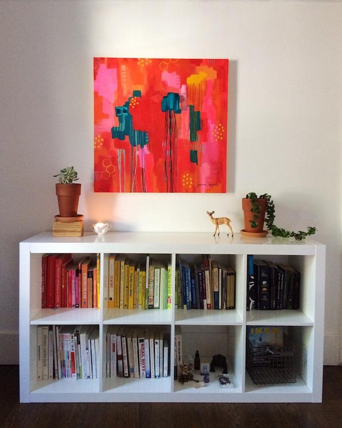 original painting with acrylics hung over bookshelf