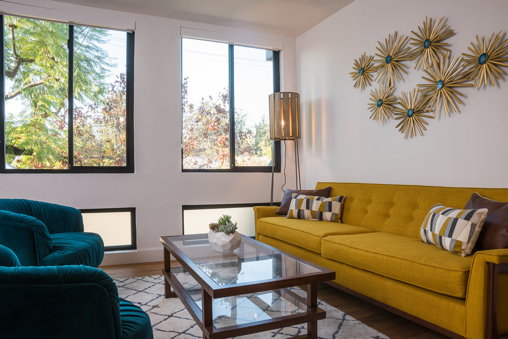 Crazy about this combination of that yellow couch and those teal velvet chairs.