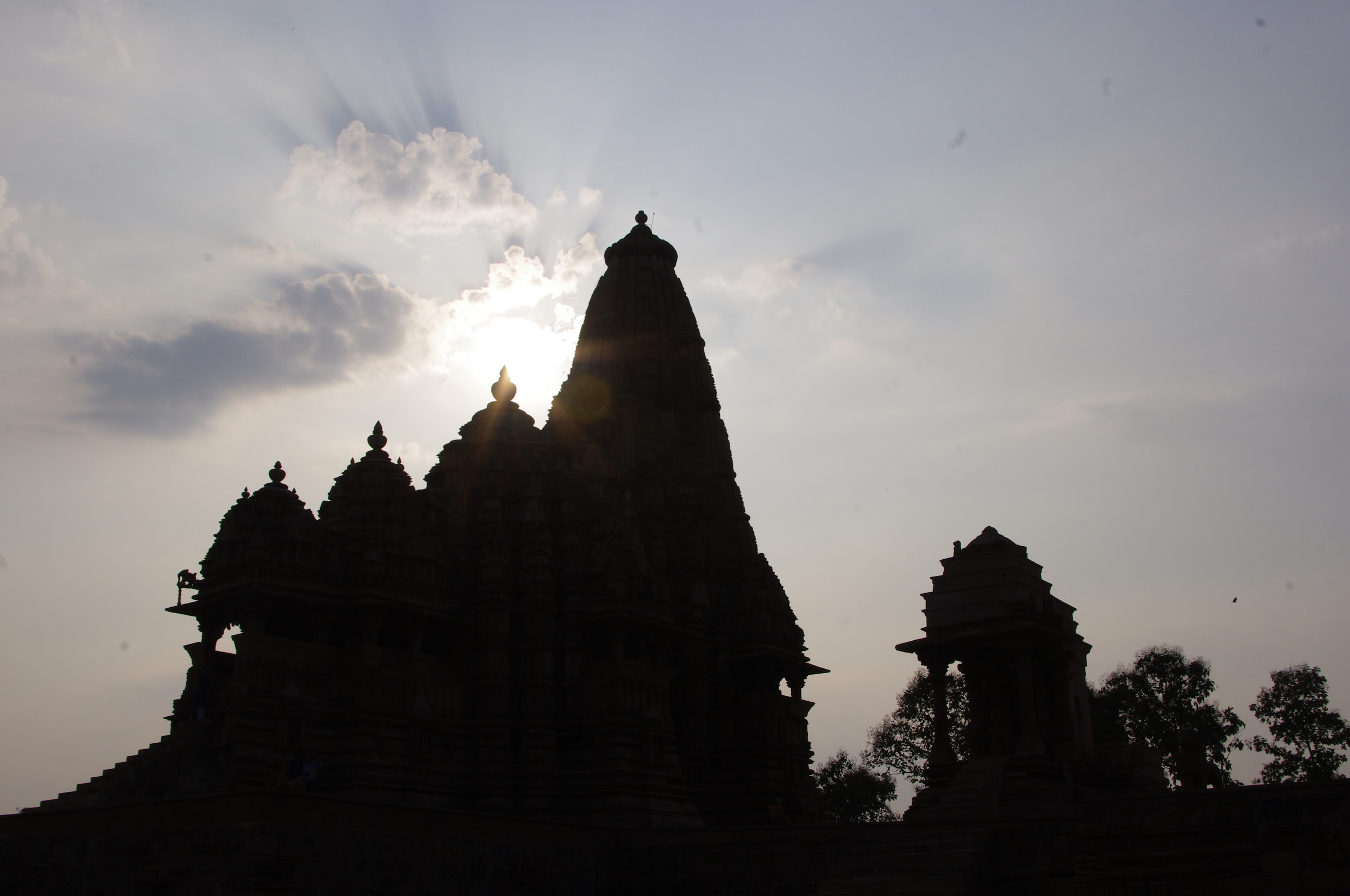 The sun setting behind a smaller group of temples.