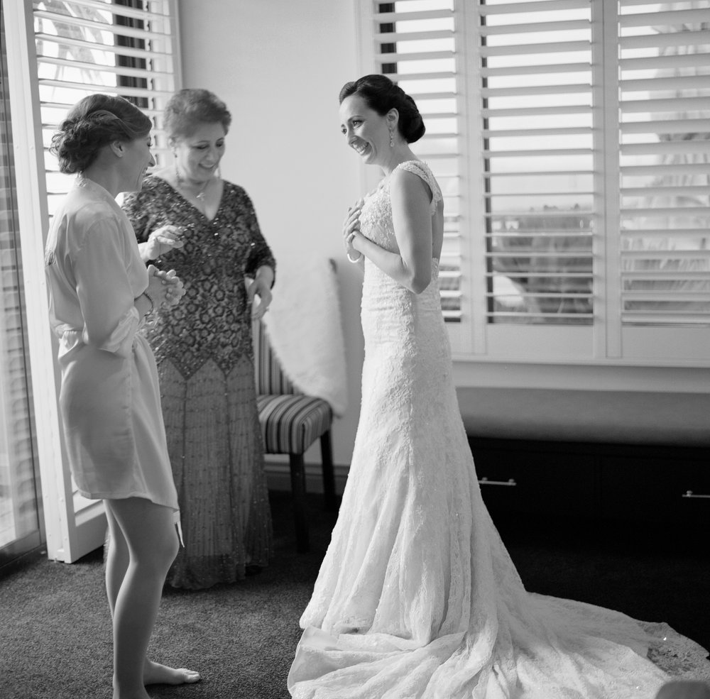The bride getting ready with her maid of honor and mother