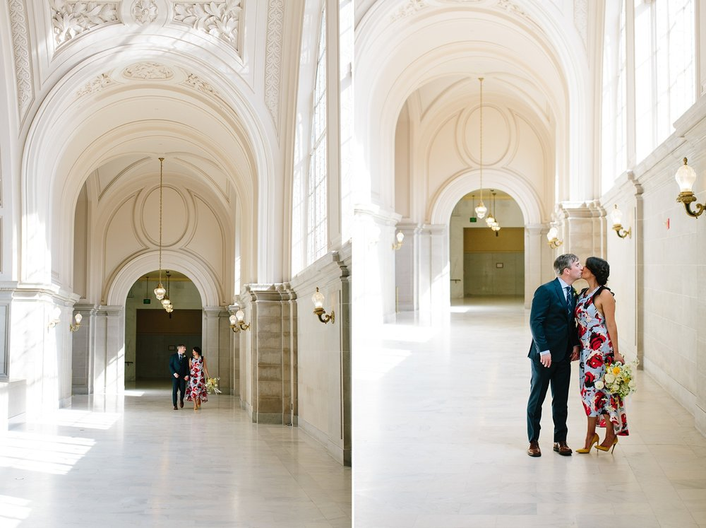 The bride and groom walk underneath the classic arches of San Francisco City Hall.