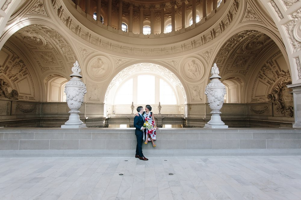 The bride sits on the 4th floor balcony with her groom under the rotunda of San Francisco's City Hall.