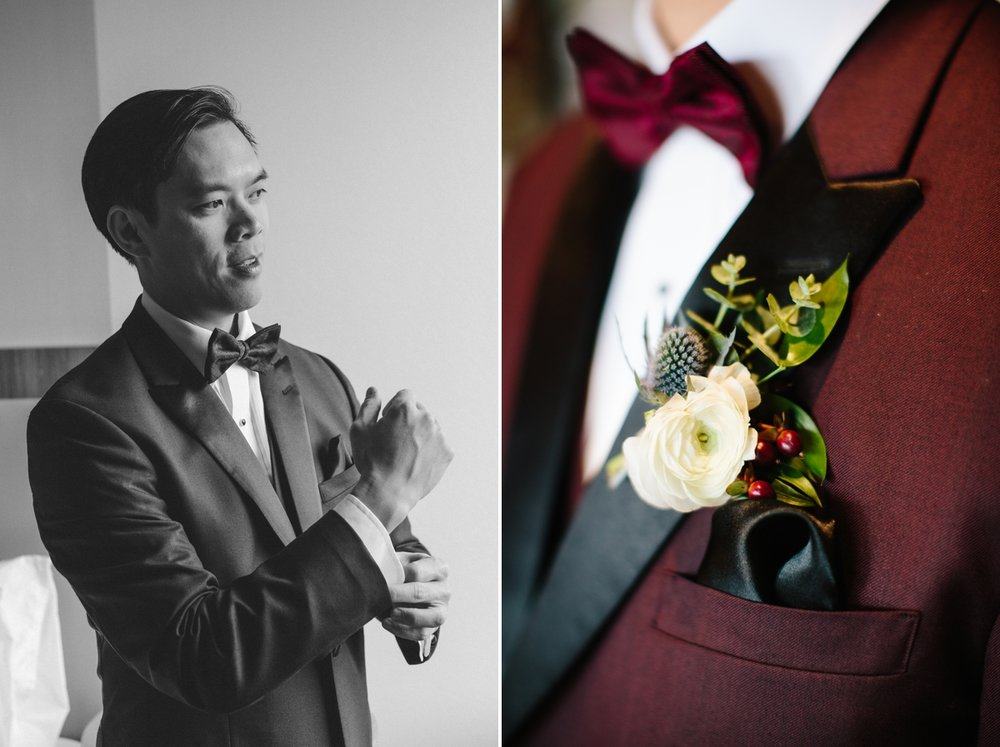 The groom puts on his burgundy tuxedo and boutonniere.