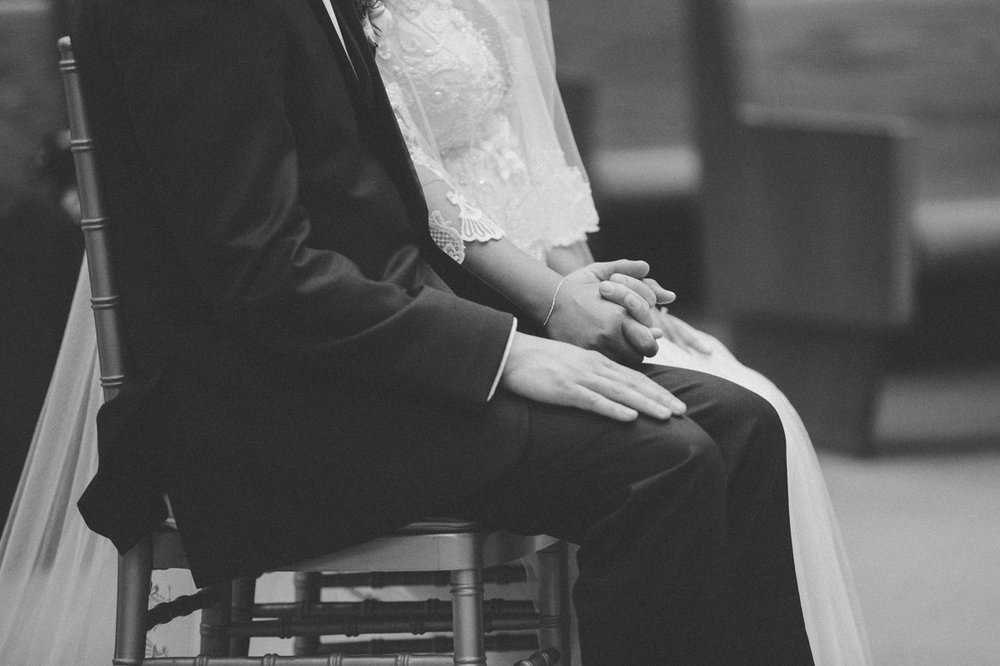 The bride and groom hold hands during the Catholic ceremony.