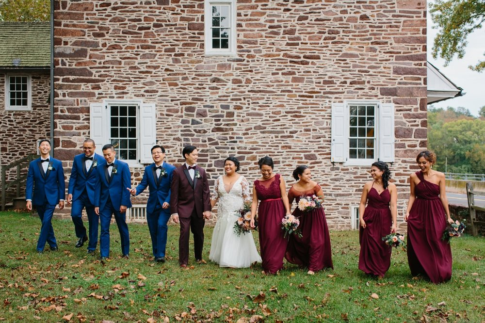 The wedding party takes a stroll in front of the historic stone buildings that sit along the Delaware river at Washington Crossing Park.