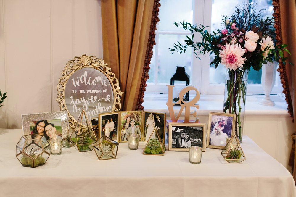 The bride and groom's wedding reception welcome table with family photos at Washington Crossing Inn.