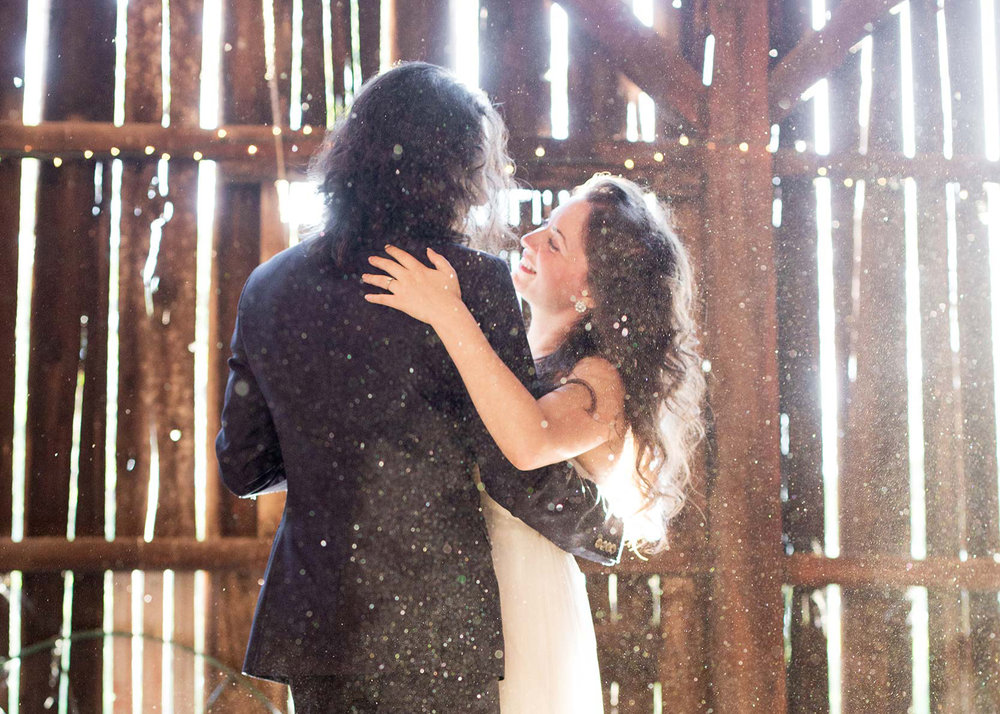 Bride and groom dancing in sunbeams in the barn during first dance at Squirrel Creek Ranch in Grass Valley.