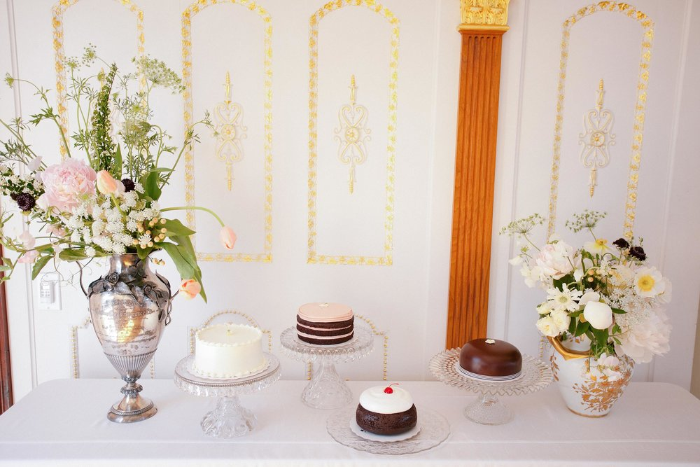Assorted mini wedding cakes from Miete bakery on display at the wedding reception in China Cabin.