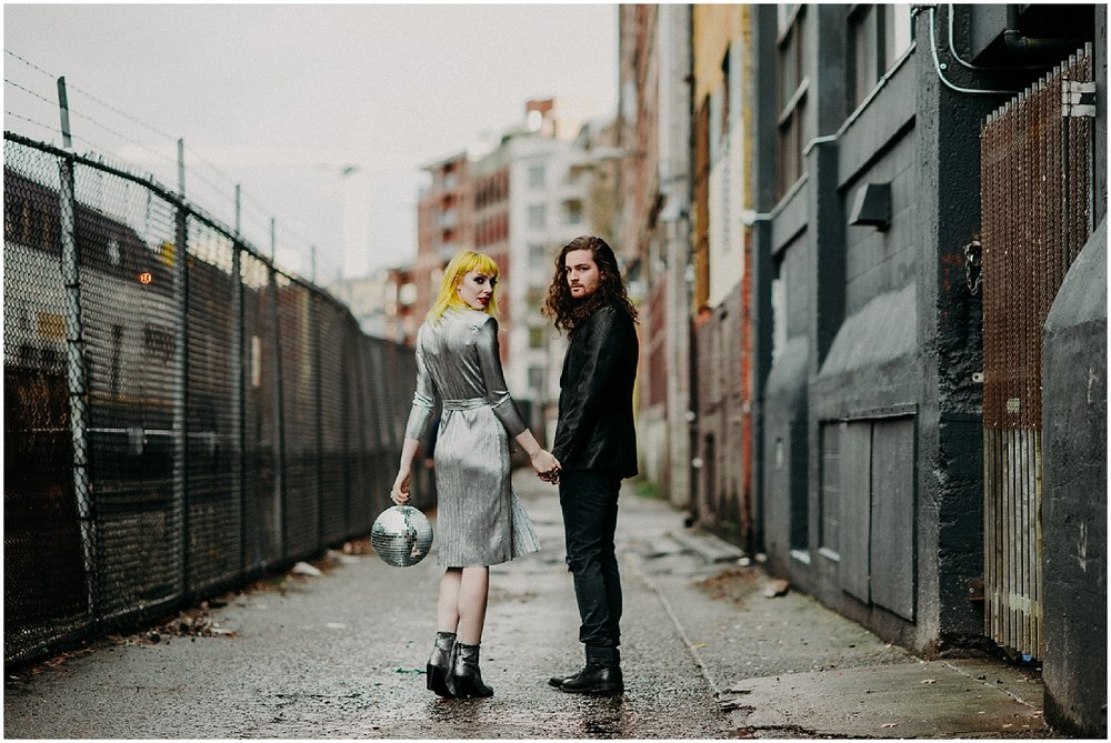 Vancouver back alley glamour grunge modern disco ball metallic dress shoes black suit curly long hair man engagement couples session concrete train chain link fence buildings