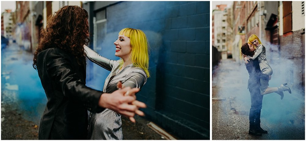 Vancouver glamour grunge back alley magic fog steam hand holding enchanting fun love smile yellow hair woman curly long locks man metallic dress style black brick wall forefront focus squeeze