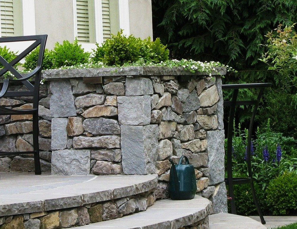 A Beautiful stone planter surrounds this elegant patio, while Basalt stairs lead down to the lawn and garden below.