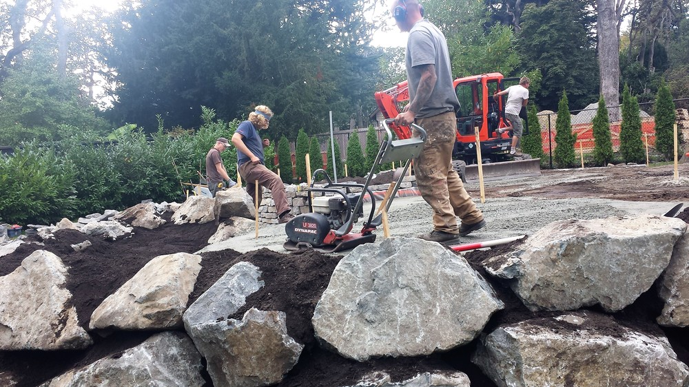 Workers build a stone retaining wall and patio.