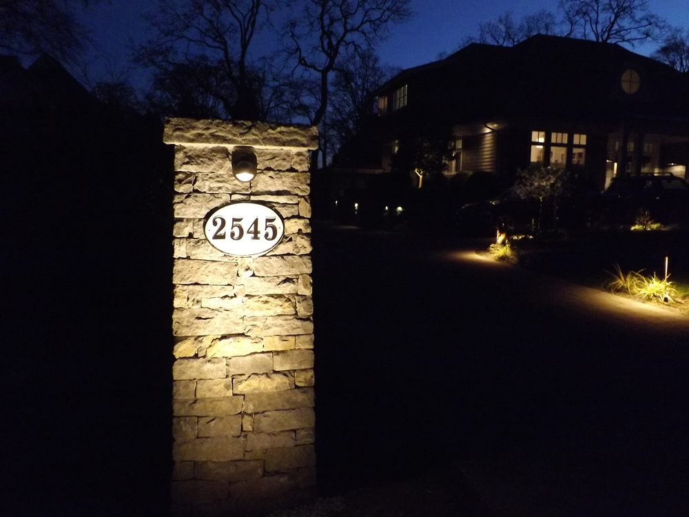 tHE LIGHTING PLAN FOR THIS LANDSCAPE INCLUDES ILLUMINATING THE bASALT ENTRANCE PILLAR AND STREET NUMBER, CASTING A WARM GLOW ALONG THE DRIVEWAY.