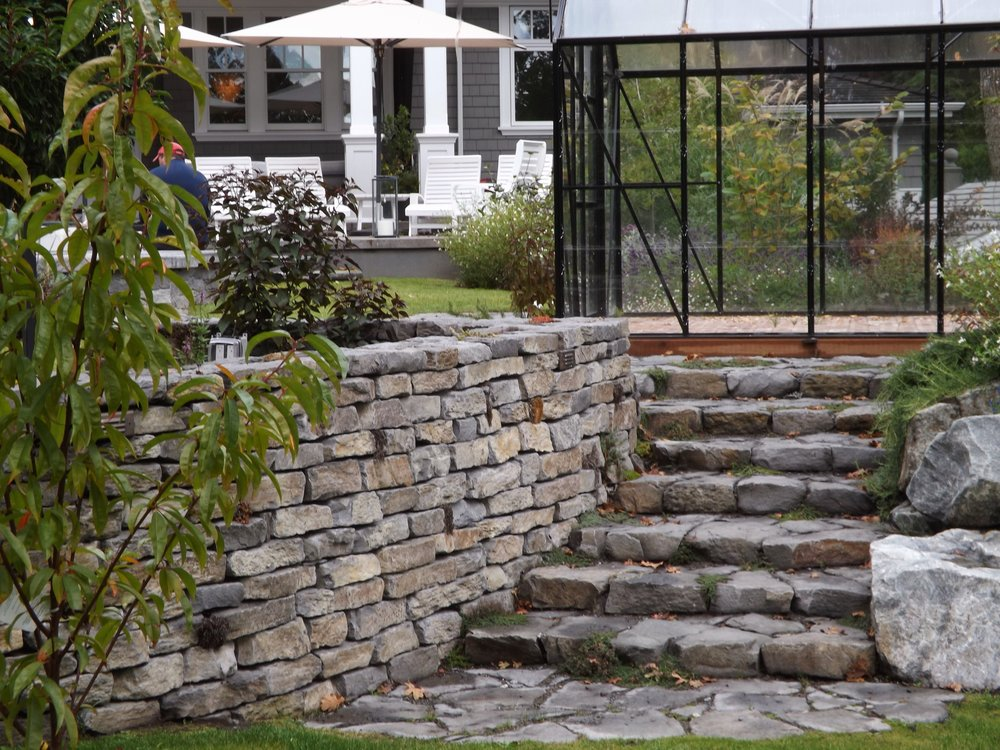 A circular rock wall and stairs made from basalt lead from the main entertaining area, featuring a spa, outdoor fireplace, BBQ and herb garden to the lower level orchard.