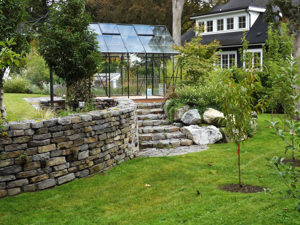 a beautiful stone wall and stairs separate the lower and orchard from the upper entertaining area, complete with spa, outdoor fireplace, patio, vegetable beds and greenhouse. landscape lighting embedded in the wall makes it easy to navigate the property at night.