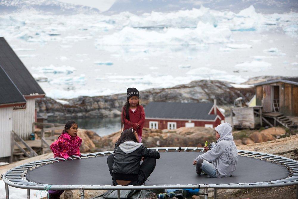 Local Greenlandic children bounce around on a trampoline.