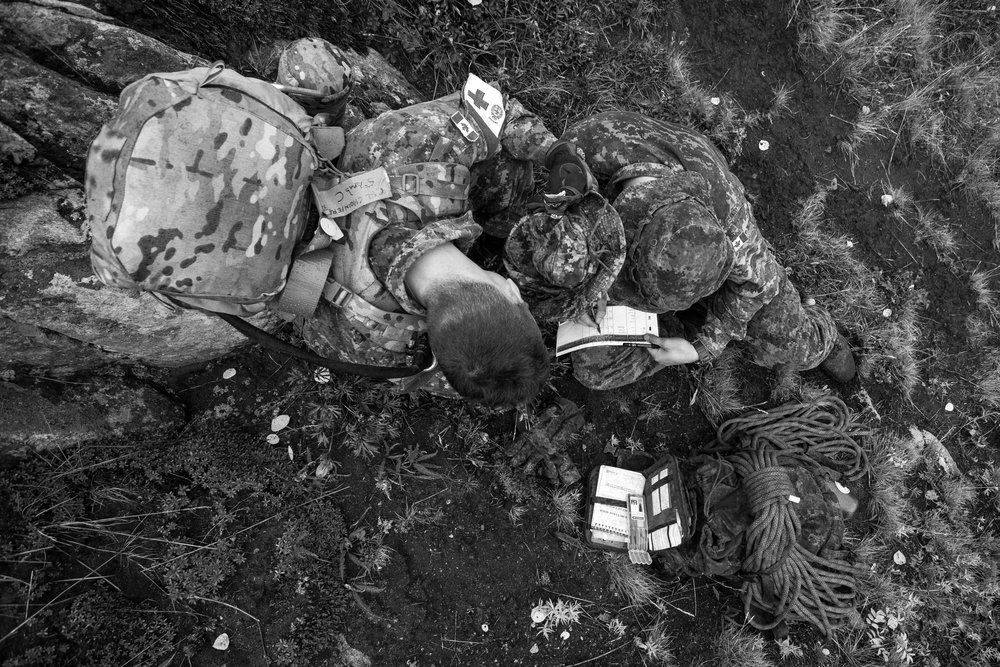 While on a hike up Paint Mountain near Haines Junction, Yukon, members of the 12e Régiment blindé du Canada from Valcartier, Quebec receive an emergency radio call regarding a fallen member back down the mountain. While one solider copies down geographic coordinates of the injured team member, another blocks the rain with his hat.