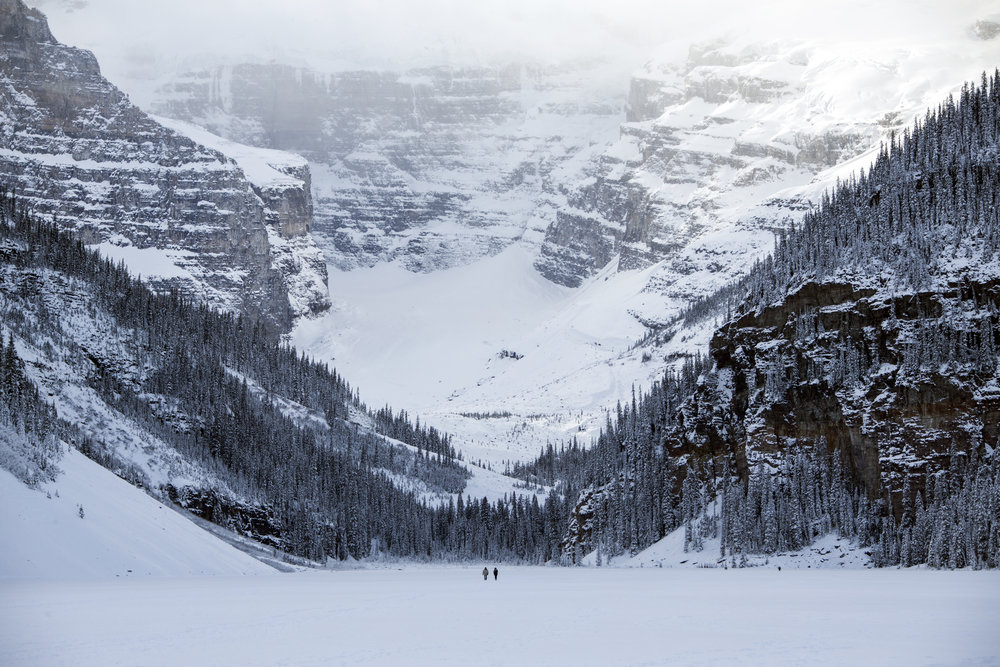 Two hikers walk across a frozen, snow covered Lake Louise, Banff National Park, Alberta.