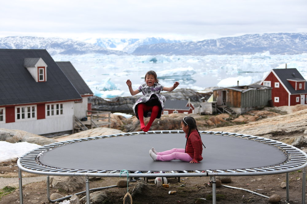 Kids bouncing on a trampoline with the ice fjord behind them in Tinit, Greenland.