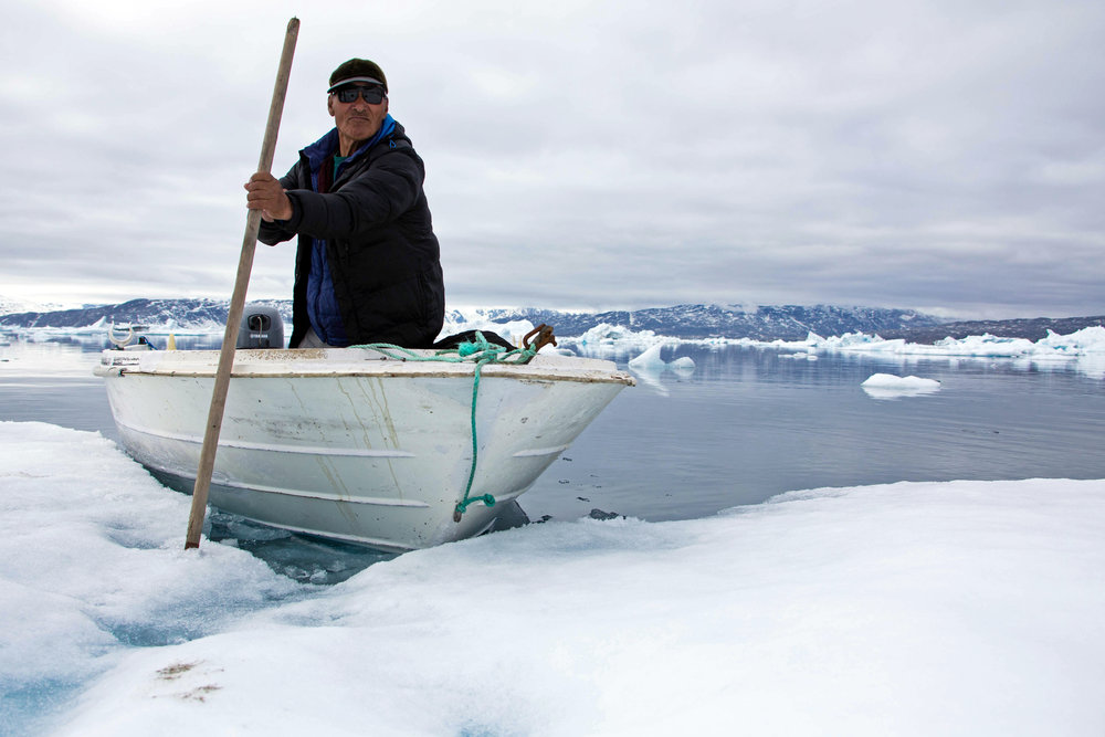 Grandpa using a spear to anchor the boat down on an iceberg in Tinit, Greenland.