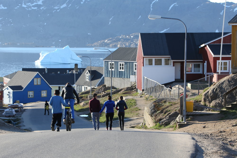 Locals walk along one of Tasiilaq's main drives, east Greenland.