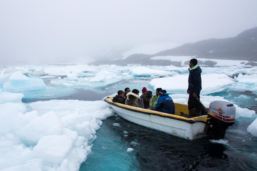 Tunu locals take a boat from Kulusuk to Kuummiit, Greenland.