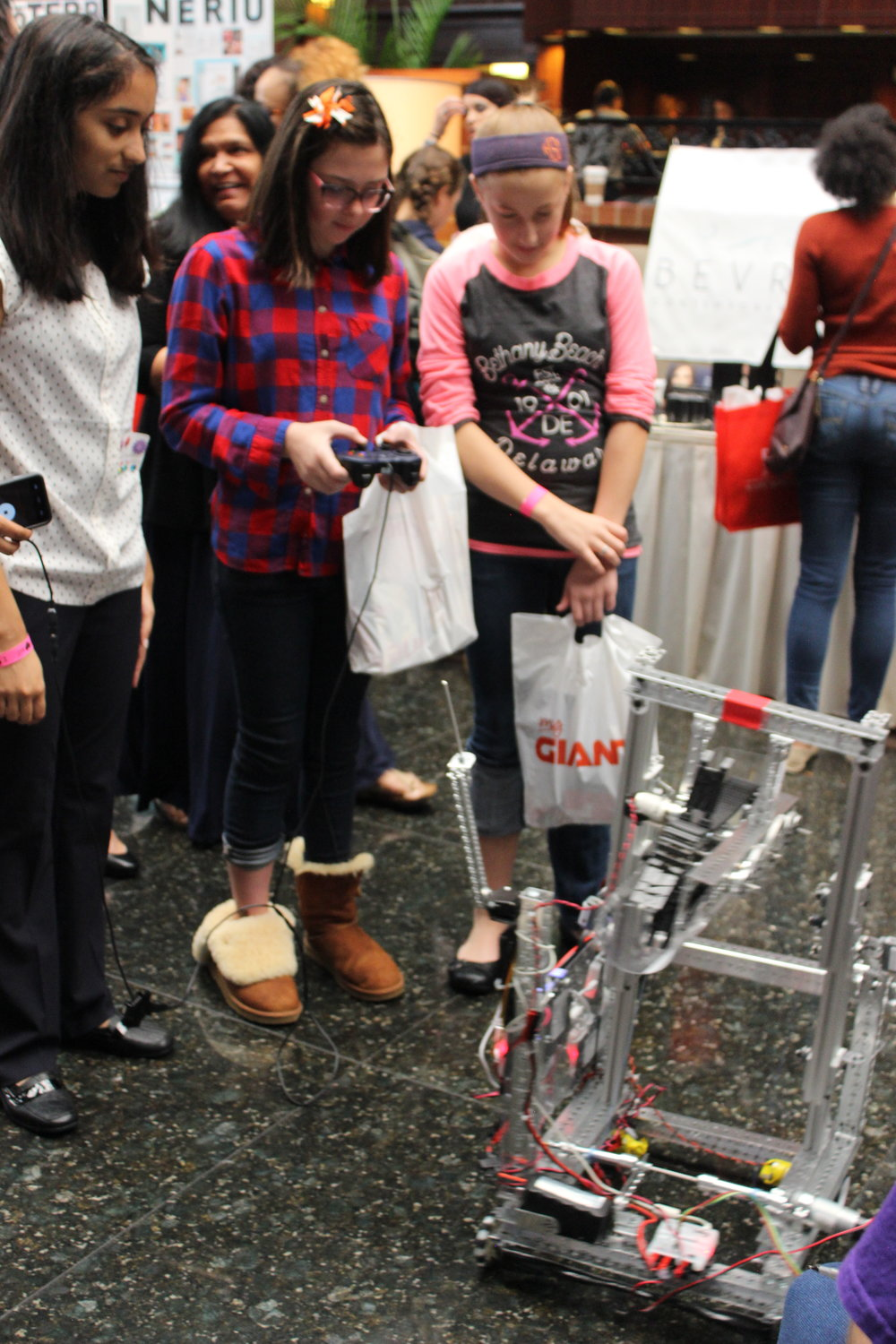 Rachael helps girls learn how to raise the robot's lift using the controllers. Girls World Expo, October 2016.