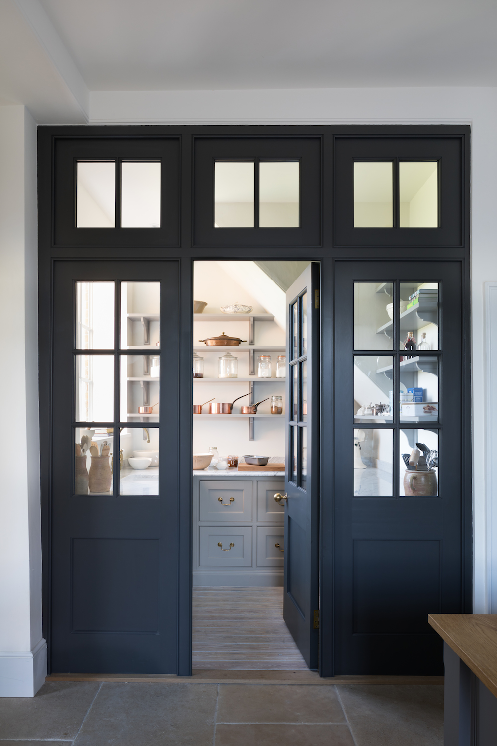 """This Georgian style """"joinery wall"""" of dark doors and glass, separate the pantry from the kitchen but creates a very elegant feature. 
