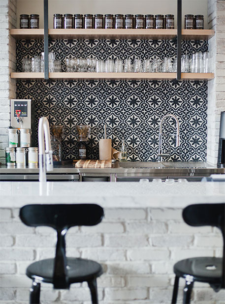 Bold black, white and grey encaustic cement tiles in this industrial-luxe cafe bar. Designed by:  Nam Dang-Mitchell