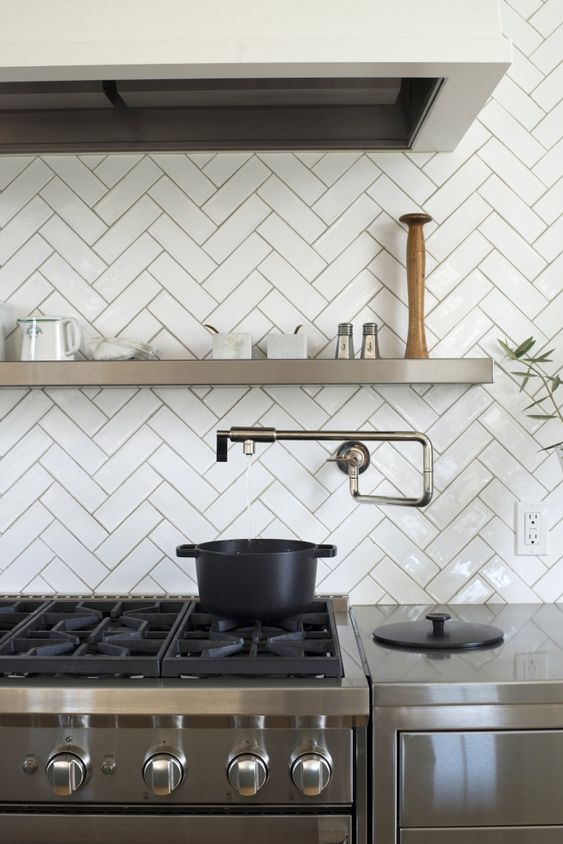 Classy gloss white herringbone tiles with a darker grout. Image credit:  Remodelista