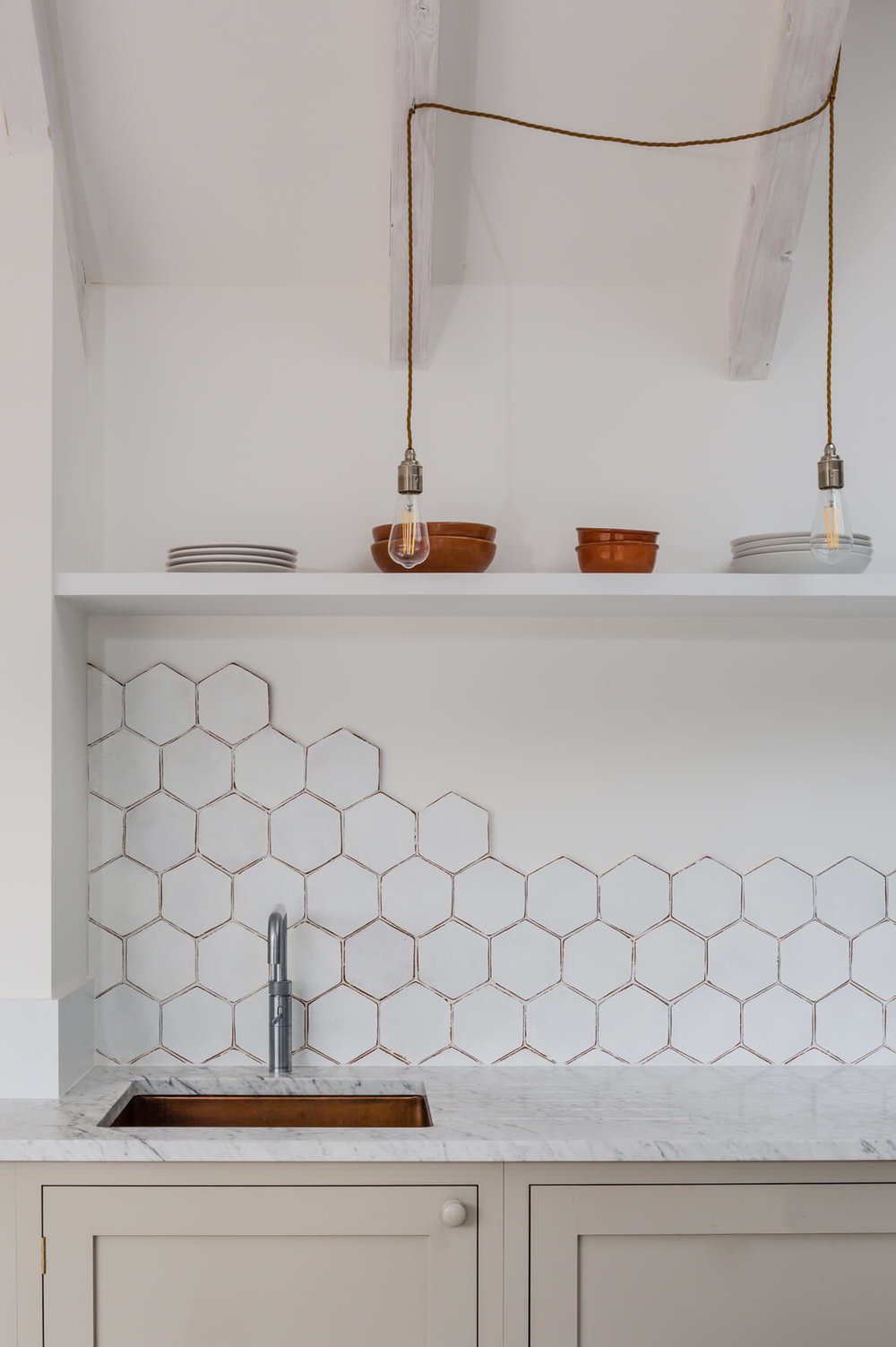 White hexagon tile, left unfinished but it looks great. Architects:  Reed Watts , Kitchen:  deVOL
