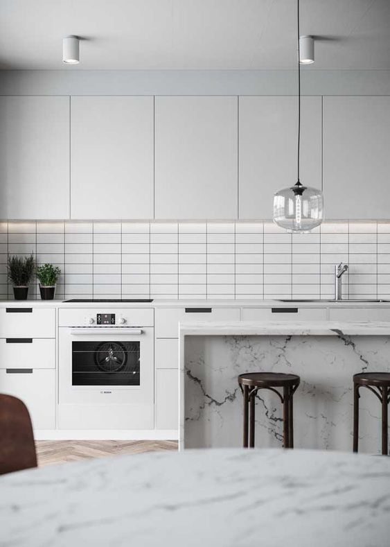 This all white kitchen is made interesting with simple grid tiles. Image source:  Decorfacil
