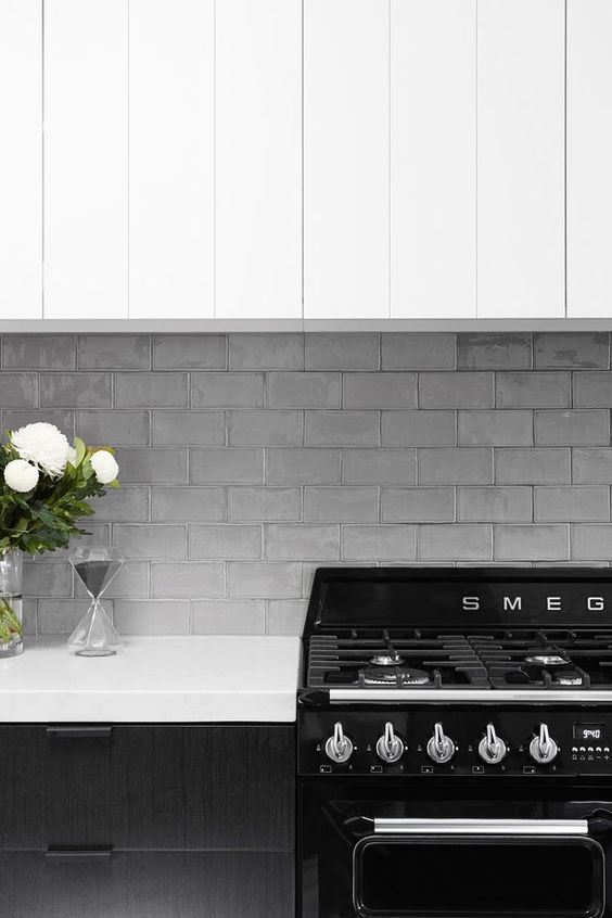 Gloss grey, vintage subway tiles are a classic pairing with a black and white kitchen. Interior Design:  Horton and Co Design