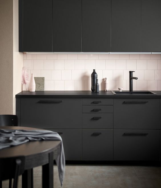 Soft pink tiled splashback with black Ikea kitchen. Here's an interesting side note, the cabinets are made from recycled plastic bottles. Industrial Design:  Form Us With Love