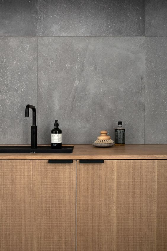 The large grey tiles and sawn cut oak have a beautiful natural texture. Kitchen is in  Norm Architects  Copenhagen studio.