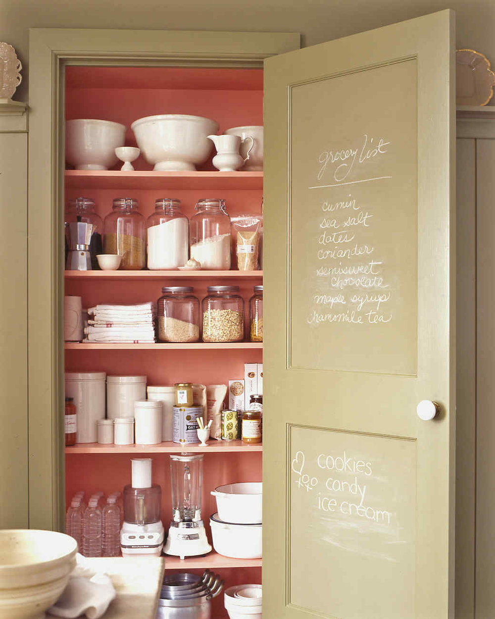 The pink interior of this pantry really draws you in. The green paint is a perfect pairing too.  Martha Stewart