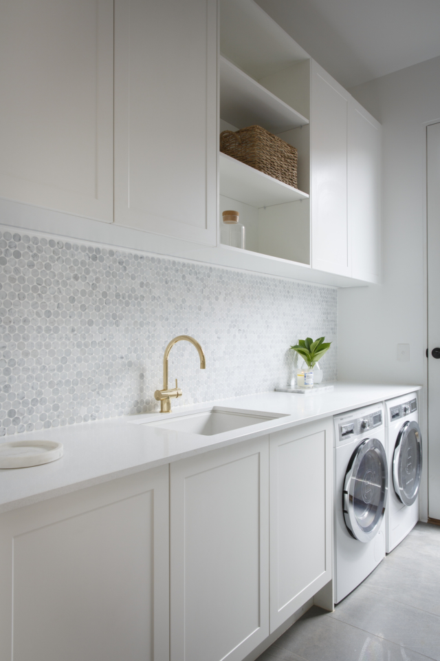 Matte white Shaker style cabinets looking classy in this beautiful laundry |  The Interiors Addict