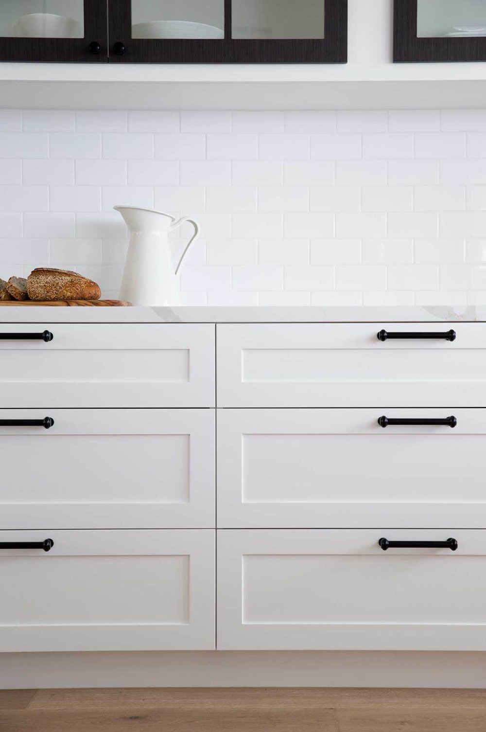 White Shaker style drawers with black bar handles in this classic kitchen |  MorrisCo Design