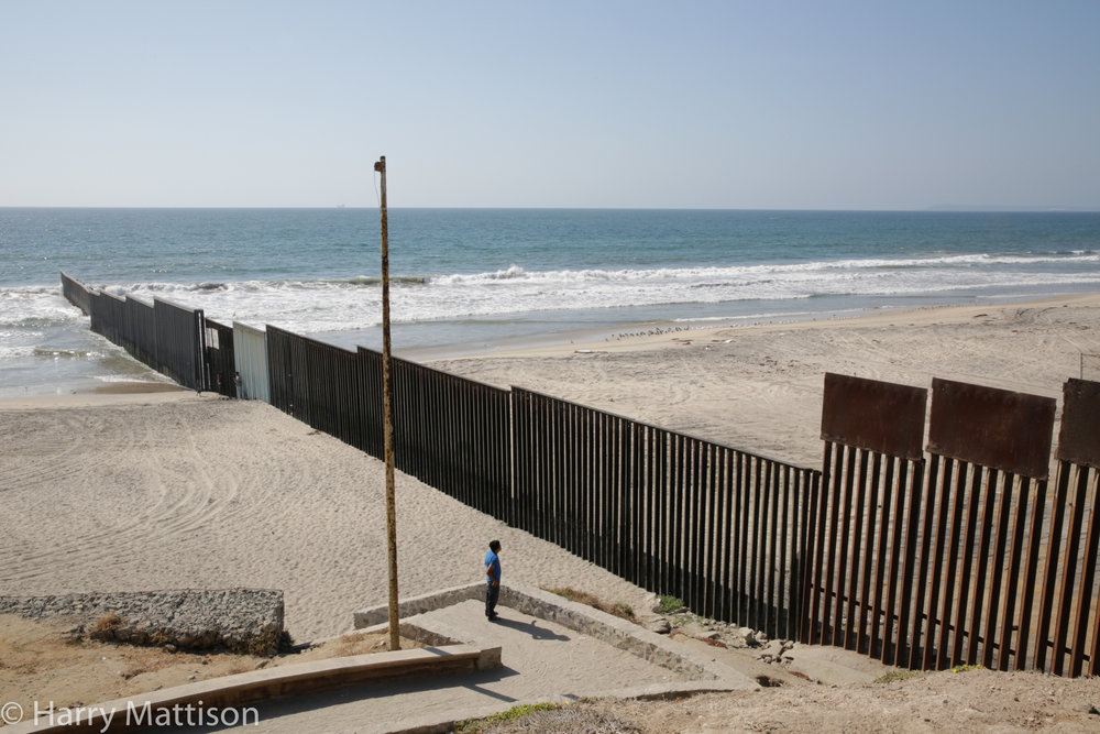 A man looking at the border fence from Playas de Tijuana towards the United States.
