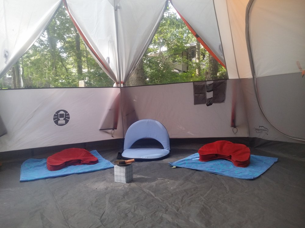 A few floor seats are set up inside our tent before meditation time.