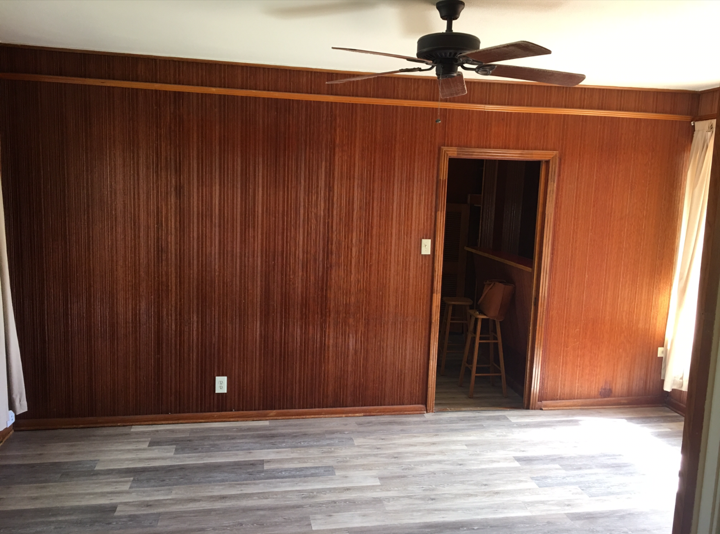 """this room is directly through the french doors, and will serve as the dining room. there is (was!) awful wood paneling in both rooms, and we have since torn it down, reframed some walls, and are eagerly awaiting drywall install. we also plan to replace the flooring (shown here is vinyl) with a warm oak that will match the original wood in the front living space and help the """"flow"""""""
