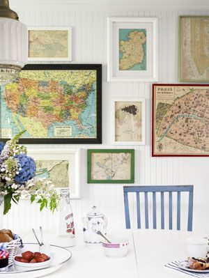 This dining area displays a really interesting and eclectic display of different maps in varying frames and colours. They work well against the white background and with the coloured chair.