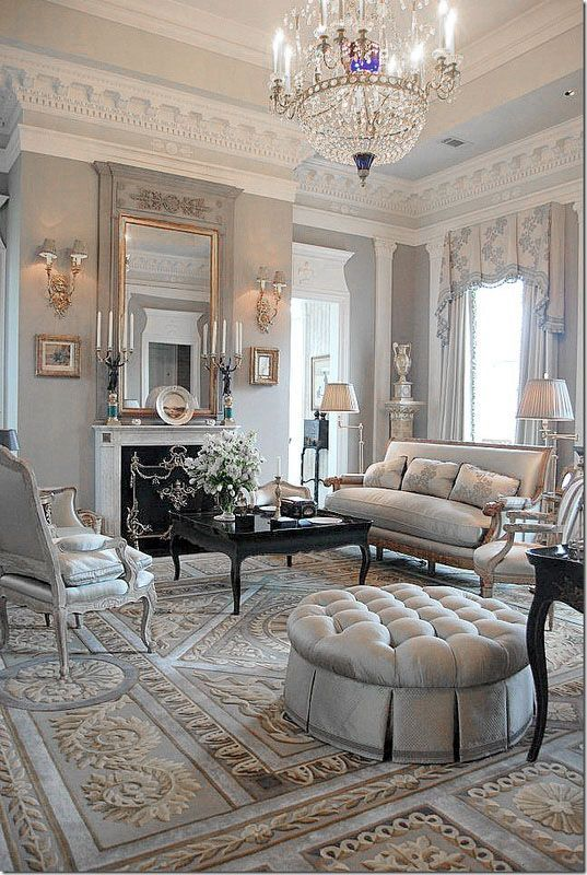 For modern tastes, there is not much desire for clutter, but a sense of opulence is still created using similar ideas to those in Victorian times. Deep buttoned upholstery, gilding, a thick rug and glass chandelier give a sense of luxury. The multi-layered widow treatment, mounted urn and emphasis on the room's ceiling height brings grandeur. The lighting is soft and the reflective surface of the coffee table, as well as the brass wall lights, candlesticks and mirror will ensure this room sparkles as evening sets in. The limited colour palette is lifted through this clever use of accessories and texture.