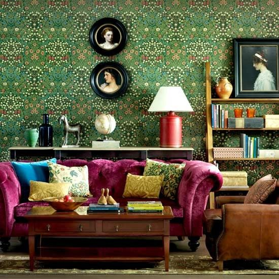 This room pays homage to Victorian styling. The patterned wallpaper and luxurious pink velvet sofa work really well. The patterned cushions unite the wallpaper and furnishings. The simple wall pictures and plain armchair and coffee table help to make this room feel comfortable and stop it from being over cluttered.